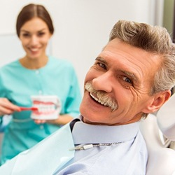 Dental team member talking about dentures with older man in dental chair