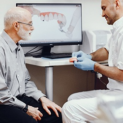 An older man watching as his dentist shows him how dentures work
