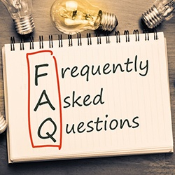 Frequently asked questions notepad with lightbulbs surrounding
