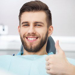 Man with thumbs up in dentist's chair after periodontal therapy