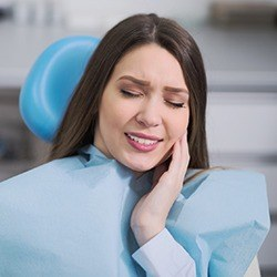 Woman in dentla chair holding jaw in pain