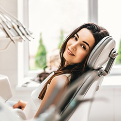 Woman in dental chair smiling after tooth extraction