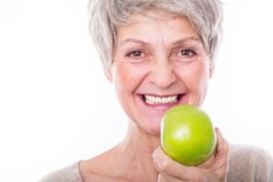 older woman holding an apple
