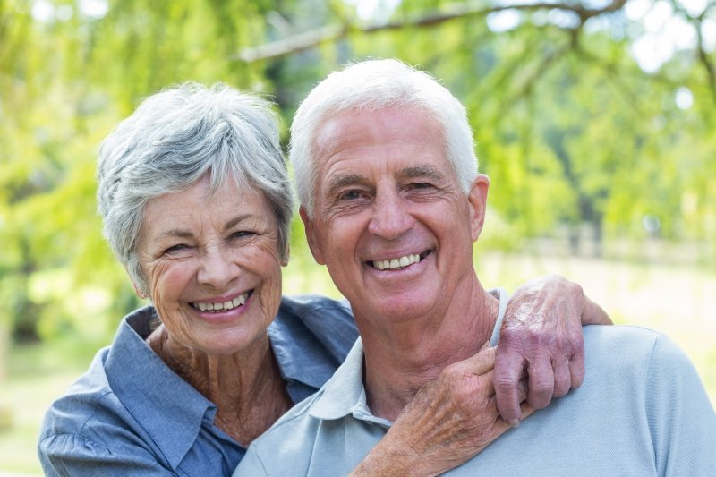 An older couple smiling after receiving implant-retained denture.