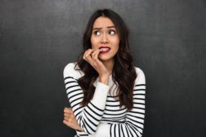 woman with dental implants in Rock Hill nervously biting her fingernails